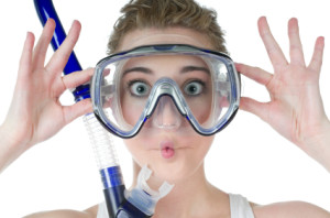 Surprised young woman, scuba mask and snorkel, makes funny fish